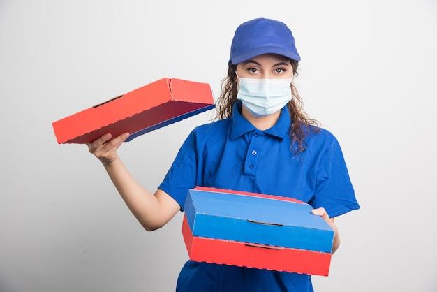 白の医療用フェイスマスクが付いた3つの箱を持ったピザ配達の女の子