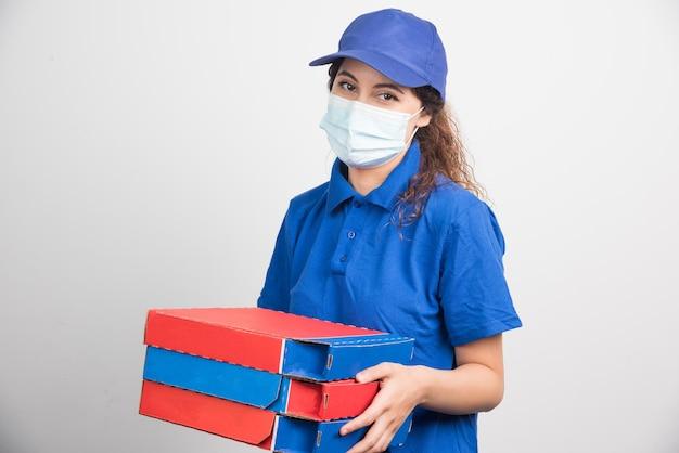 Доставка пиццы держит три коробки с медицинской маской на белом