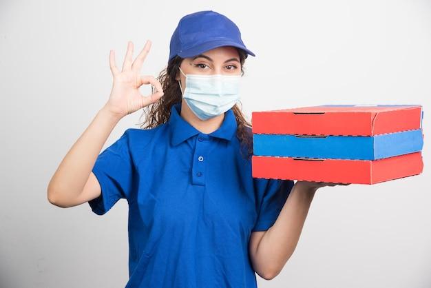 Ragazza che consegna la pizza in possesso di tre scatole con maschera facciale medica che mostra gesto ok su bianco