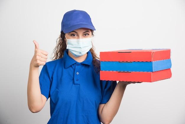 Ragazza che consegna la pizza in possesso di tre scatole con maschera facciale medica che mostra pollice in su su bianco