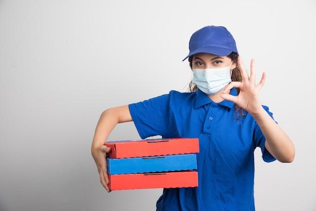 La ragazza che consegna la pizza tiene in mano tre scatole con una maschera medica e mostra un gesto ok su bianco