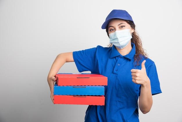 La ragazza delle consegne della pizza tiene in mano tre scatole con una maschera medica e mostra il pollice su bianco on