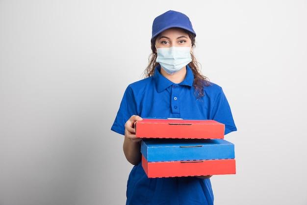Ragazza delle consegne della pizza che tiene tre scatole con maschera facciale medica su bianco