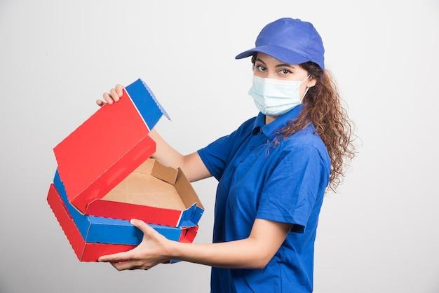 La ragazza delle consegne della pizza apre una delle scatole di pizza con una maschera medica su bianco