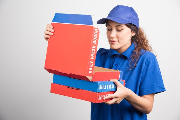 白い背景の上のピザの箱の1つを開くピザ配達の女の子