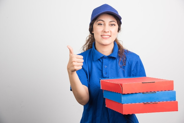 Ragazza di consegna pizza che mostra pollice in su con scatole di pizza su sfondo bianco