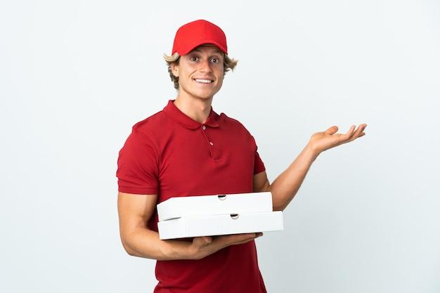 Доставщик пиццы на изолированном белом фоне, протягивая руки в сторону, приглашая приехать