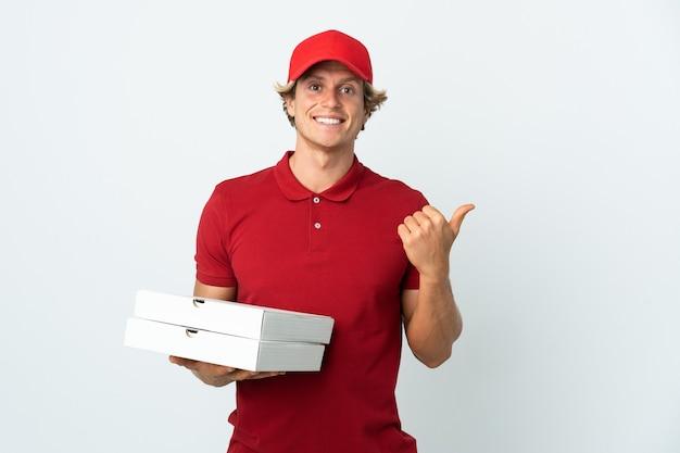 제품을 제시하기 위해 측면을 가리키는 격리 된 흰 벽 위에 피자 배달 남자