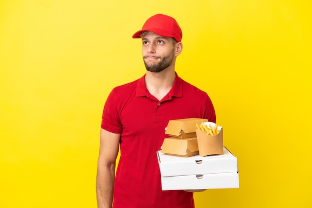 孤立した背景の上にピザの箱やハンバーガーを拾って見上げるピザ配達人