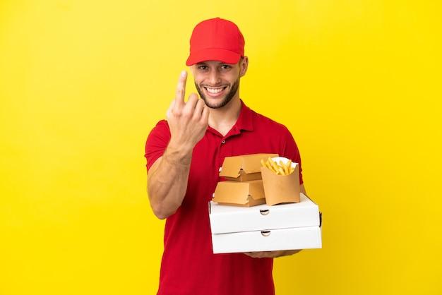 来るジェスチャーをしている孤立した背景の上にピザの箱やハンバーガーを拾うピザ配達人