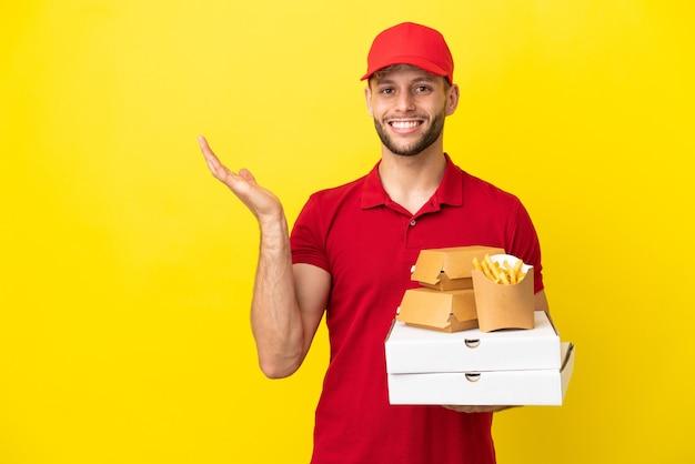 Доставщик пиццы собирает коробки из-под пиццы и гамбургеры на изолированном фоне, протягивая руки в сторону, приглашая приехать
