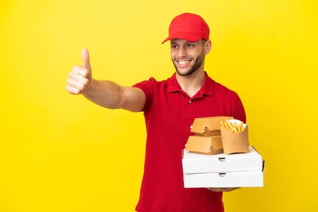 孤立した背景の上にピザの箱やハンバーガーを拾って親指を立てるジェスチャーを与えるピザ配達人