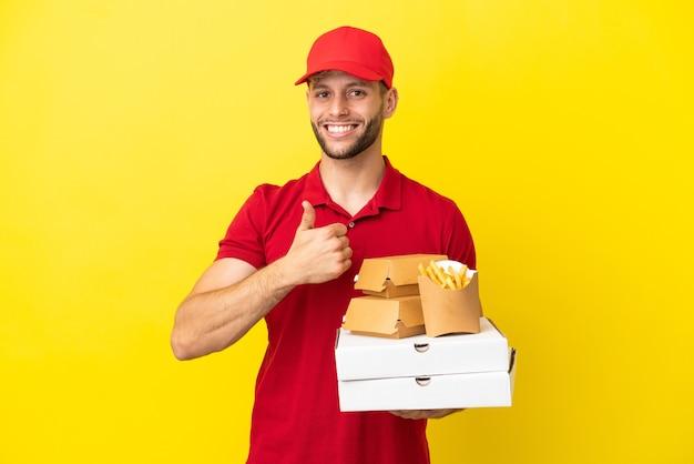 Доставщик пиццы собирает коробки для пиццы и гамбургеры на изолированном фоне, показывая жест рукой