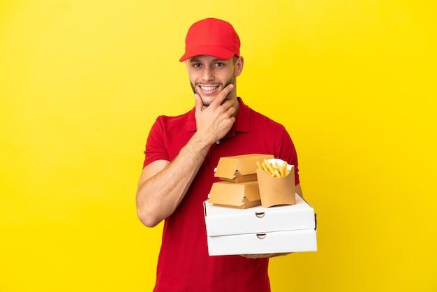 Доставщик пиццы собирает коробки для пиццы и гамбургеры на изолированном фоне, счастливые и улыбающиеся