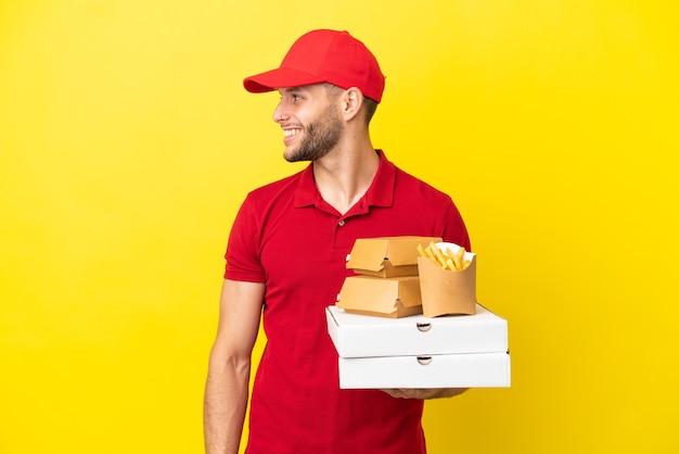 Доставщик пиццы собирает коробки для пиццы и гамбургеры на изолированном фоне, смеясь в боковом положении