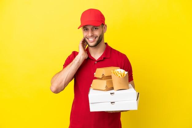 Доставщик пиццы собирает коробки для пиццы и гамбургеры на изолированном фоне, смеясь
