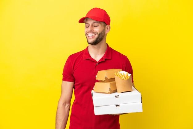 笑っている孤立した背景の上にピザの箱やハンバーガーを拾うピザ配達人