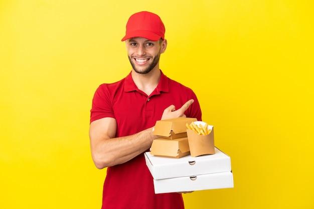 後ろ向きの孤立した背景の上にピザの箱やハンバーガーを拾うピザ配達人