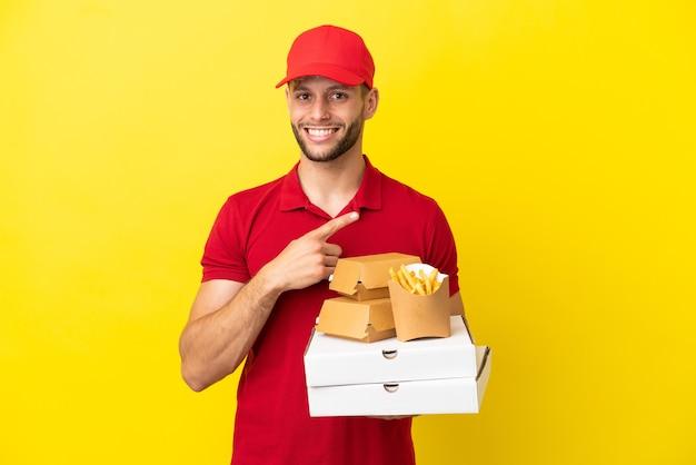 製品を提示する側を指している孤立した背景の上にピザの箱やハンバーガーを拾うピザ配達人