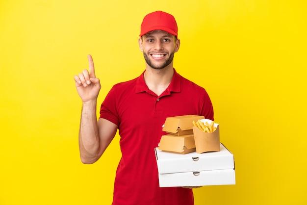 素晴らしいアイデアを指している孤立した背景の上にピザの箱やハンバーガーを拾うピザ配達人