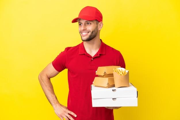 腰に腕と笑顔でポーズをとって孤立した背景の上にピザの箱とハンバーガーを拾うピザ配達人