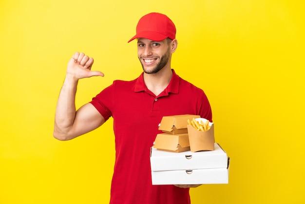 誇らしげで自己満足の孤立した背景の上にピザの箱やハンバーガーを拾うピザ配達人