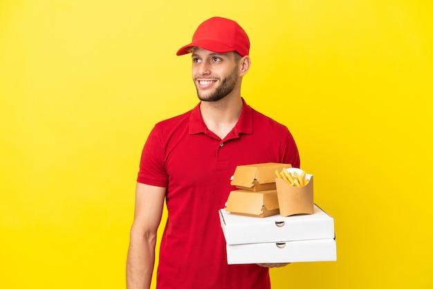 見上げながらアイデアを考えて孤立した背景の上にピザの箱やハンバーガーを拾うピザ配達人