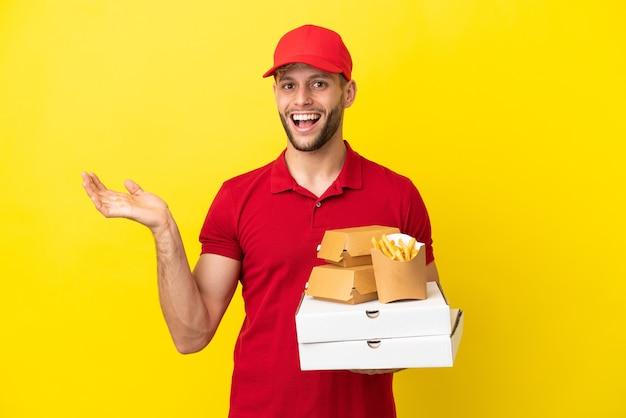 Доставщик пиццы собирает коробки для пиццы и гамбургеры на изолированном фоне с шокированным выражением лица