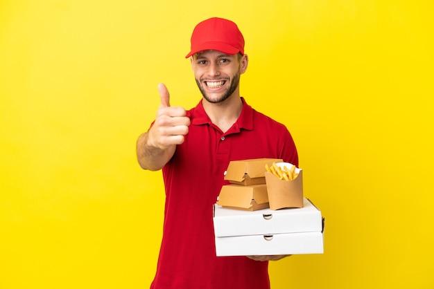 何か良いことが起こったので、親指を立てて孤立した背景の上にピザの箱やハンバーガーを拾うピザ配達人