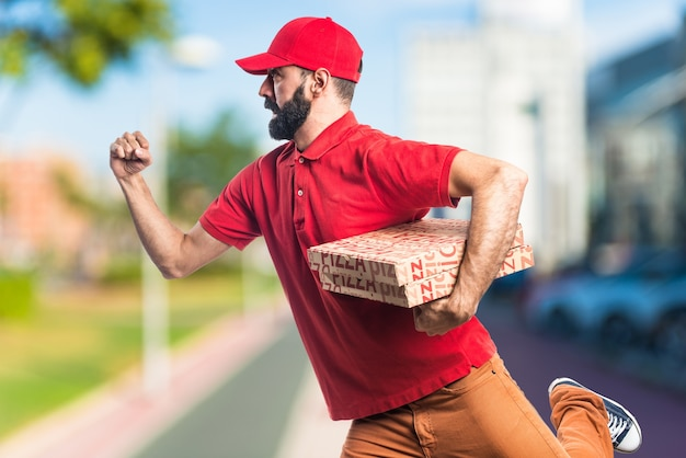 Pizza delivery man running fast on unfocused background