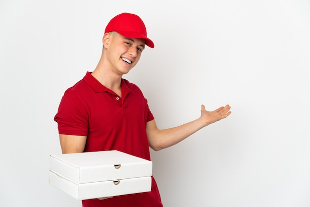 흰색 벽에 고립 된 피자 상자를 따기 작업 제복을 가진 피자 배달 남자는 올 초대를 위해 손을 옆으로 확장