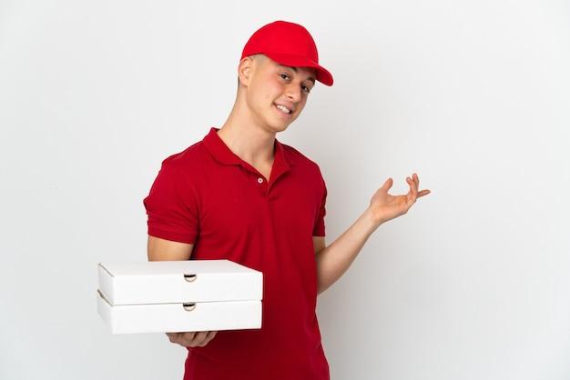 작업 제복을 가진 피자 배달 남자는 와서 초대하기 위해 손을 옆으로 확장 흰 벽에 고립 된 피자 상자를 따기