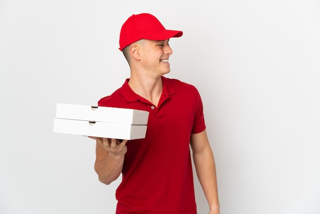 작업 제복을 가진 피자 배달 남자는 측면을 찾고 흰 벽에 고립 된 피자 상자를 따기