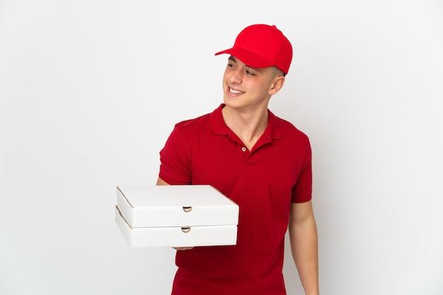 작업 제복을 가진 피자 배달 남자는 측면을보고 웃 고 흰 벽에 고립 된 피자 상자를 따기