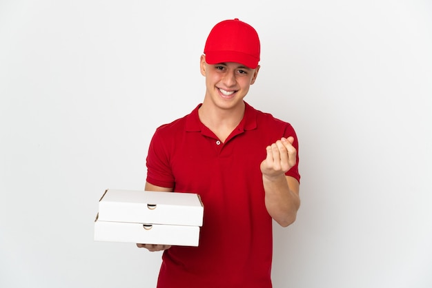 お金のジェスチャーを作る白い壁に分離されたピザの箱を拾う仕事の制服を着たピザ配達人
