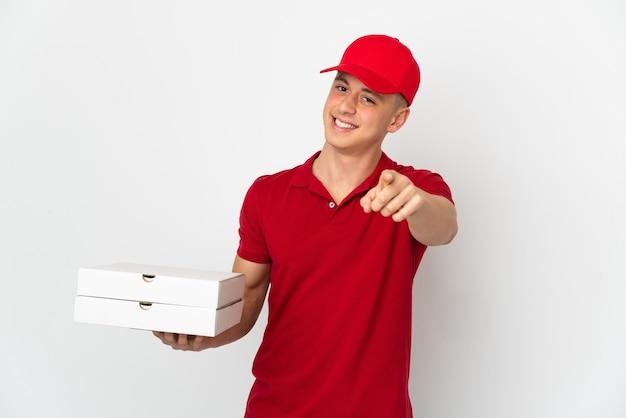 행복 한 표정으로 앞을 가리키는 흰 벽에 고립 된 피자 상자를 따기 작업 유니폼 피자 배달 남자