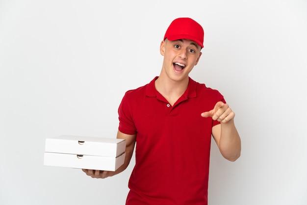 흰 벽에 고립 된 피자 상자를 따기 작업 유니폼과 피자 배달 남자는 놀라게하고 앞을 가리키는