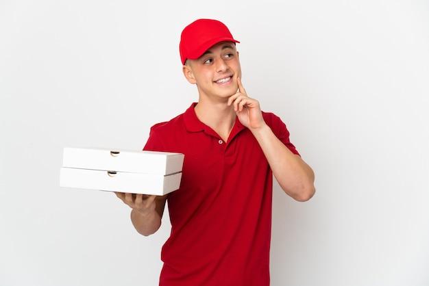 찾는 동안 아이디어를 생각하는 흰 벽에 고립 된 피자 상자를 따기 작업 유니폼 피자 배달 남자 프리미엄 사진