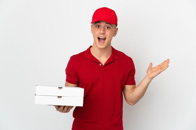 충격 된 표정으로 흰색에 고립 된 피자 상자를 따기 작업 제복을 가진 피자 배달 남자