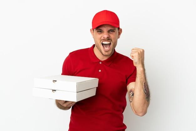 Доставщик пиццы в рабочей форме собирает коробки из-под пиццы над изолированной белой стеной, празднуя победу в позиции победителя