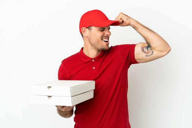 Доставщик пиццы в рабочей форме собирает коробки из-под пиццы над изолированной белой стеной, празднуя победу