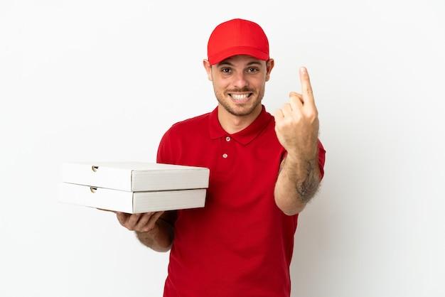 Доставщик пиццы в рабочей форме собирает коробки для пиццы над изолированной белой стеной, делая приближающийся жест