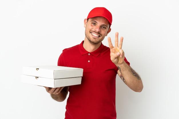 幸せな孤立した白い壁の上のピザの箱を拾い、指で3つを数える仕事の制服を着たピザ配達人