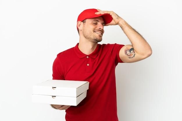 Доставщик пиццы в рабочей униформе, собирающий коробки из-под пиццы над изолированной белой стеной, кое-что понял и намеревается найти решение