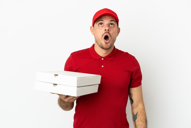 Доставщик пиццы в рабочей униформе собирает коробки для пиццы над изолированной белой стеной, глядя вверх и с удивленным выражением лица