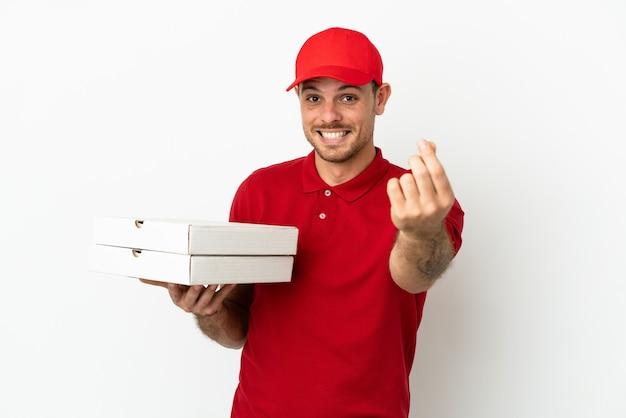 Доставщик пиццы в рабочей форме собирает коробки для пиццы над изолированной белой стеной, делая денежный жест