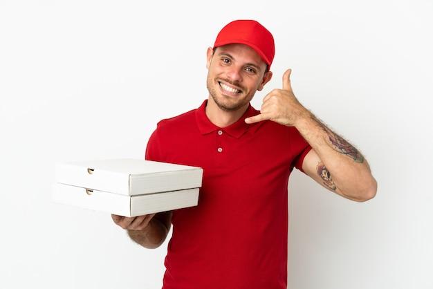 Доставщик пиццы с рабочей формой собирает коробки для пиццы над изолированной белой стеной, делая телефонный жест. перезвони мне знак