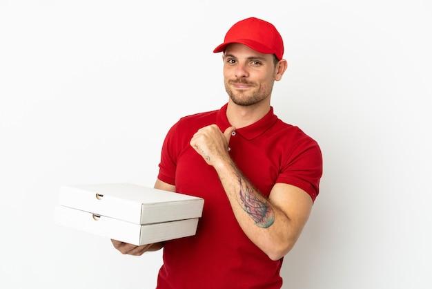 Доставщик пиццы в рабочей форме собирает коробки для пиццы над изолированной белой стеной, гордый и самодовольный