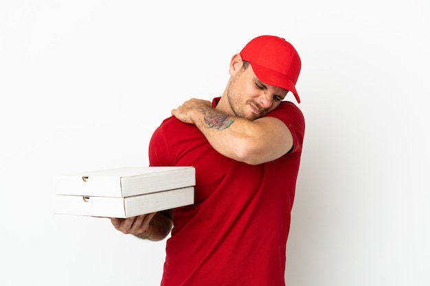 Доставщик пиццы в рабочей форме собирает коробки из-под пиццы над изолированной белой стеной и страдает от боли в плече из-за того, что приложил усилие