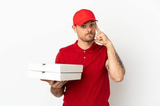 Доставщик пиццы в рабочей форме собирает коробки для пиццы над изолированной белой стеной, думая об идее